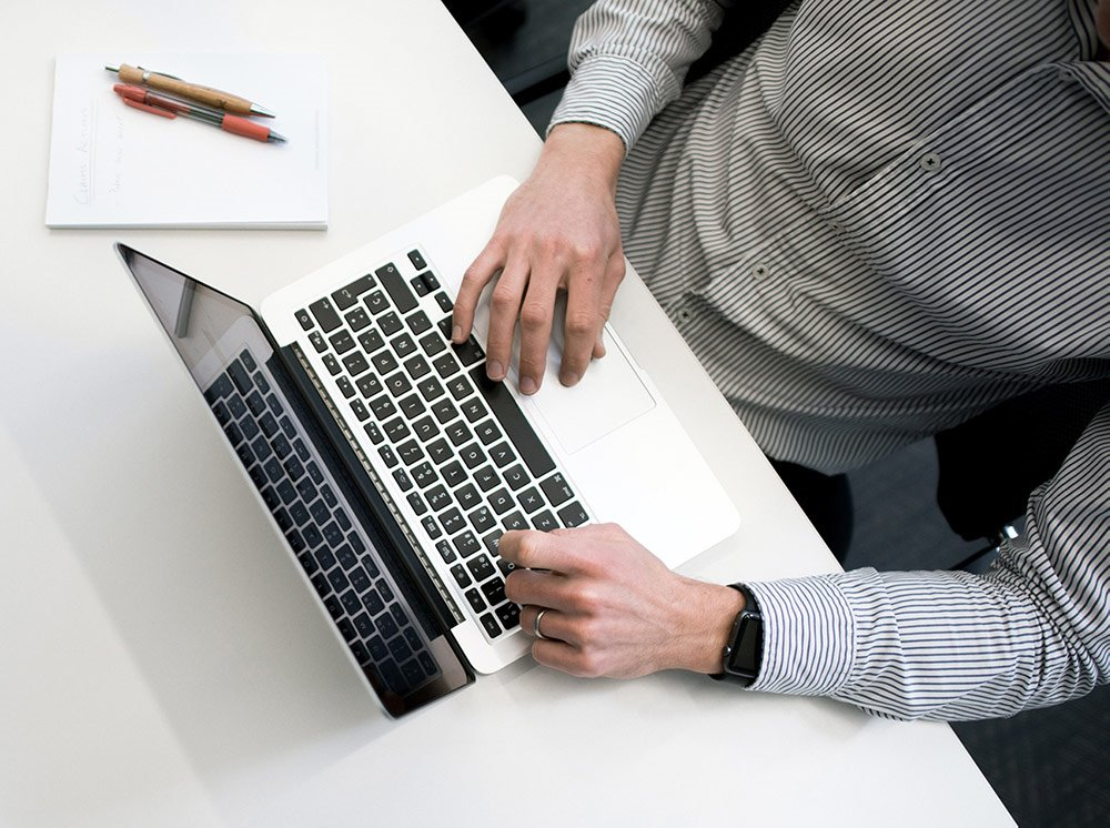 Photo of hands typing on laptop keyboard